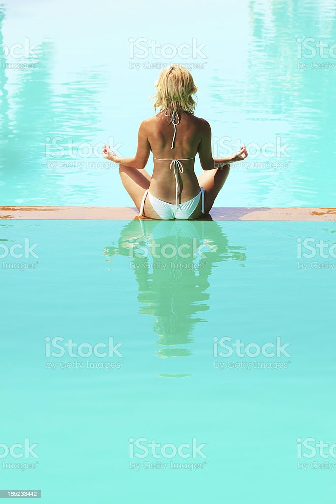 Rear view.Woman meditating on edge of swimming pool. royalty-free stock photo