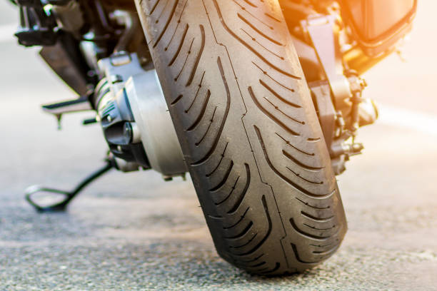 Rear wheel of sports motorcycle on road. Motorbike parked on a street. Freedom and travel concept. Rear wheel of sports motorcycle on road. Motorbike parked on a street. Freedom and travel concept. motorcycles stock pictures, royalty-free photos & images