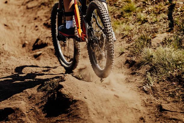 paseos en bicicleta de deporte de rueda trasera en el polvo de la tierra - foto de stock