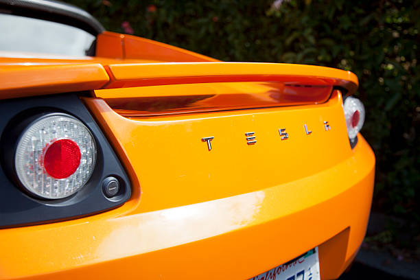 Rear-end view of an orange convertible Palo Alto, California, USA - July 19, 2011: An exterior look at the rear end of an orange convertible Tesla Roadster electric sports car. The Roadster was designed in partnership with Lotus and debuted in 2008 and had a sticker price of around $100,000 dollars. Tesla plans to continue to sell the cars through 2012. tesla motors stock pictures, royalty-free photos & images