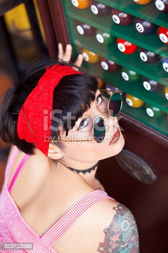 Rearshot portrait of thai girl with tattoos and sunglasses at cabinet with pool balls
