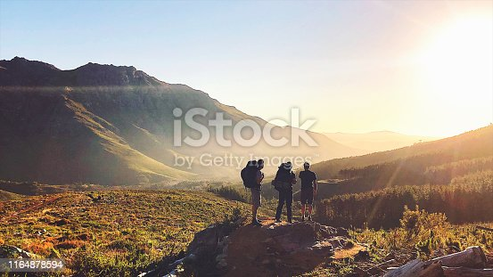 Rearview of Hikers with backpacks enjoying the sunset in the mountains Stellenbosch Cape Town South Africa
