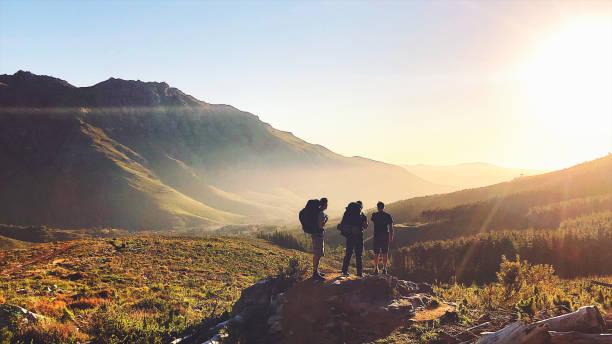 vista retrovisora de los excursionistas con mochilas disfrutando de la puesta de sol en las montañas - excursionismo fotografías e imágenes de stock