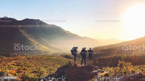 Photo of Rearview of Hikers with backpacks enjoying the sunset in the mountains