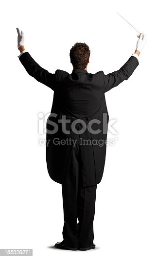 A rear view of a music conductor dressed in tails in the act of conducting.  Against a white backdrop there is room for copy space.  He stands in a formal position, arms raised and gloves on his hands.  He is ready to conduct an orchestra or symphony.  The conductor demands attention.