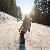 Rearview shot of a snowboarder riding the slope in the mountains on a beautiful winter sunny day sunlight flare recreation. Ski season and winter sports concept