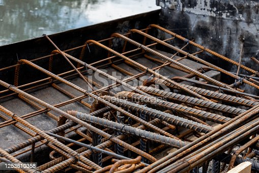 Rebar tie wire work at construction site. Steel bars reinforcing for reinforced concrete and building structures.