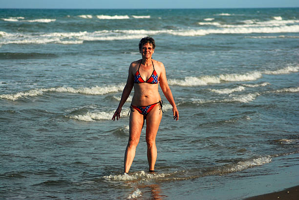 Rebel Girl Mature woman wearing a swim suit resembling the rebel flag stands in the surf of the gulf of mexico. middle aged women in bikinis stock pictures, royalty-free photos & images