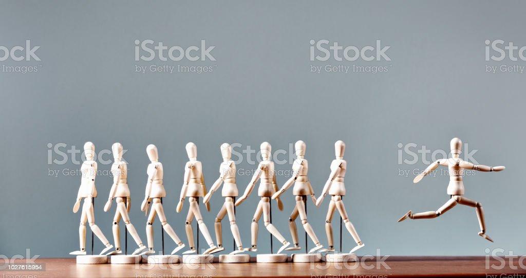 Rebel: single marionette breaks away from line of marchers stock photo