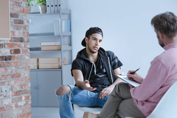 A rebel teenage boy with behavioral problems and criminal past talking to a psychotherapist in a juvenile detention center. stock photo