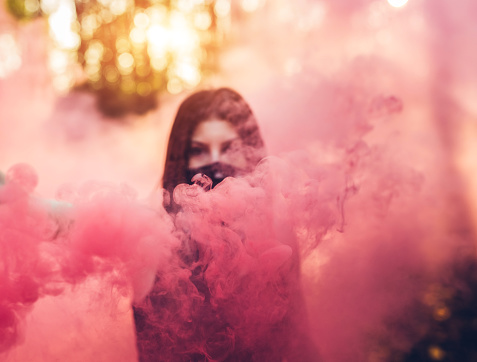 Woman with bandana holding color smoke fountain in the forest.