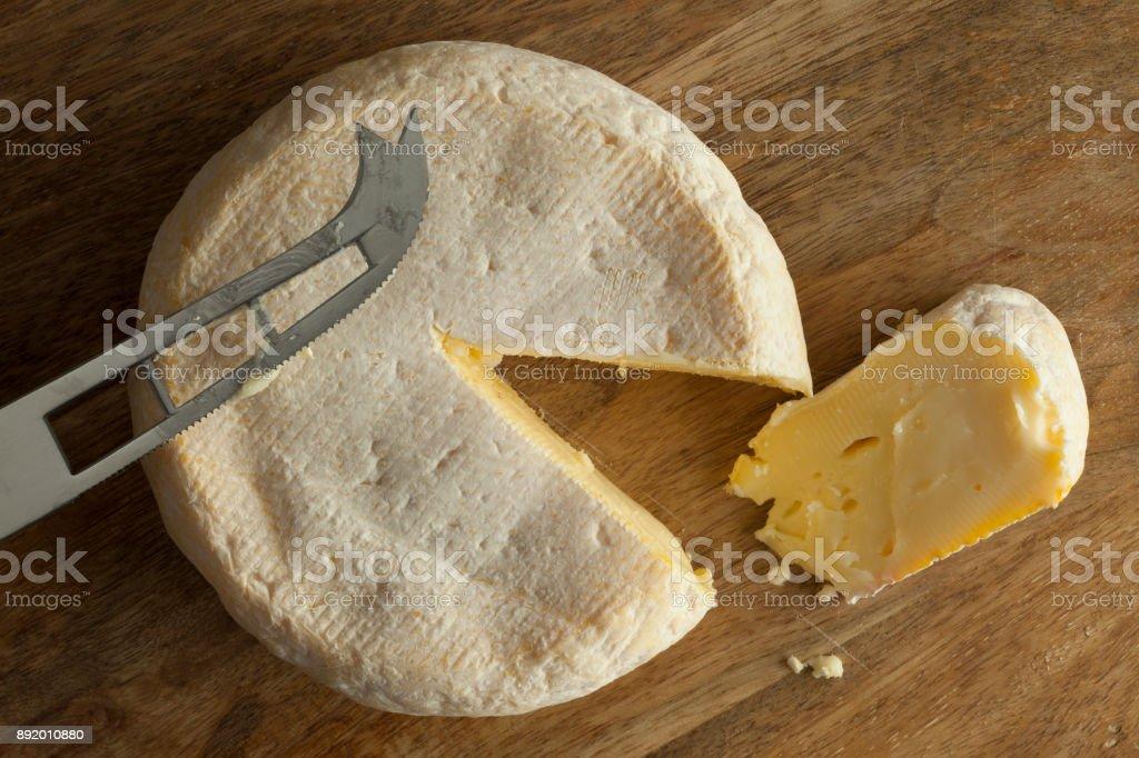 Reblochon de Savoie cheese with a slice stock photo