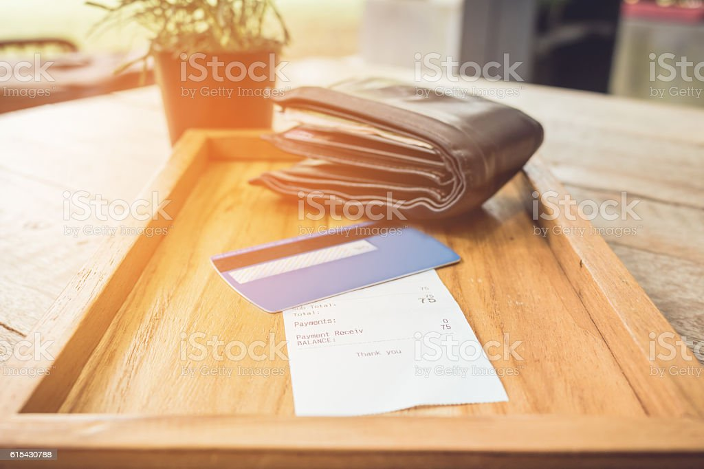 Receipt and credit card with wallet on wooden vintage tone. stock photo