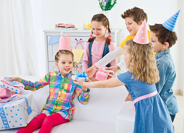 Receiving birthday presents Happy children at Birthday Party. Four cute kids coming to their girlfriend at birthday party and giving to her many presents. group of friends giving gifts to the birthday girl stock pictures, royalty-free photos & images