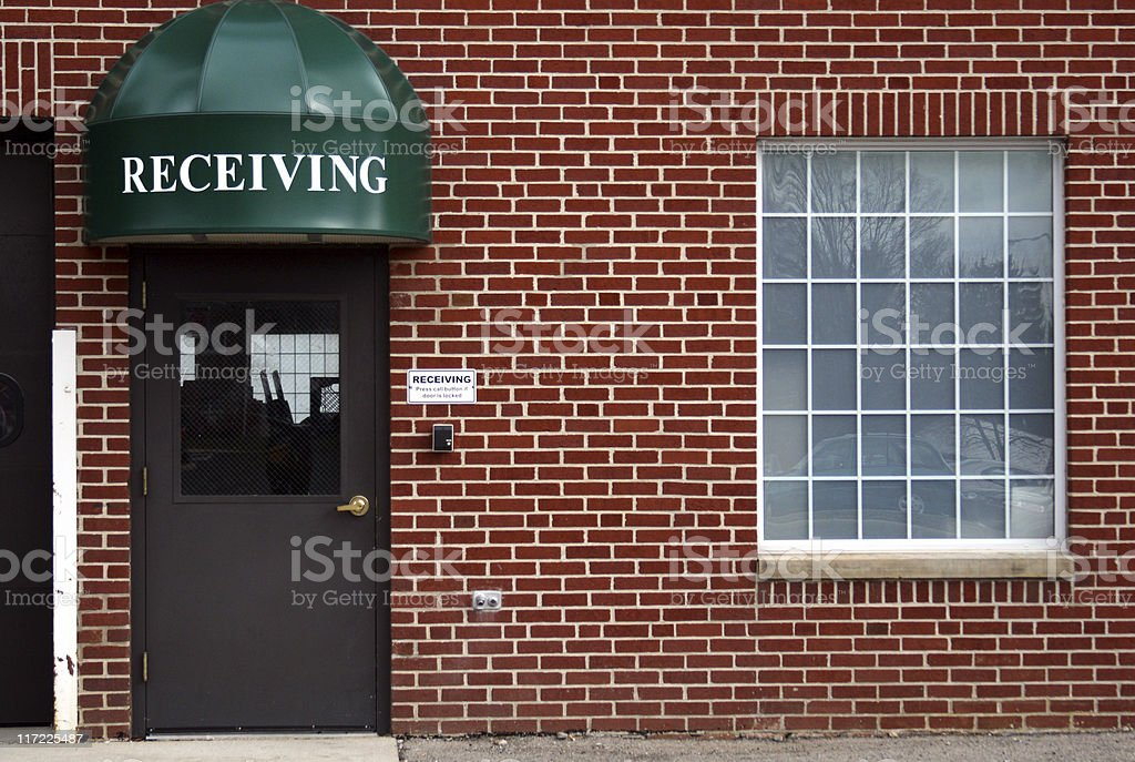 Receiving door and a brick wall in Urban setting Background stock photo