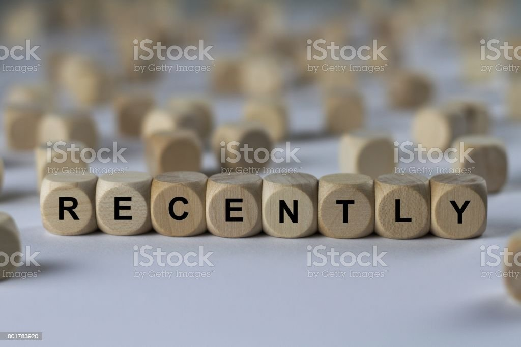 recently - cube with letters, sign with wooden cubes stock photo