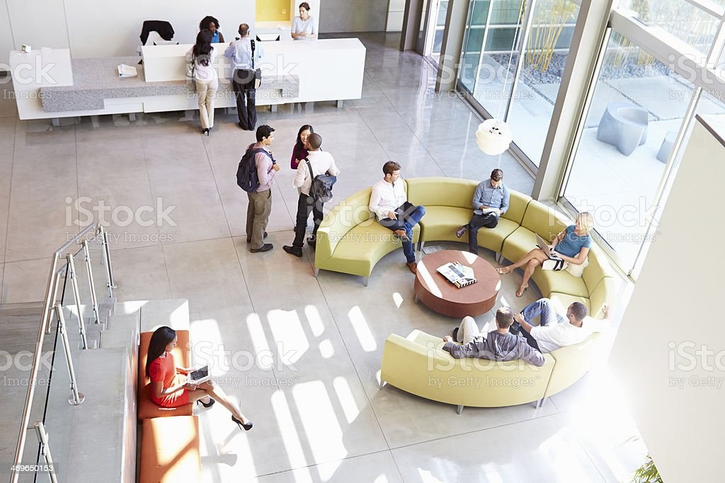 Reception Area Of Modern Office Building With People stock photo