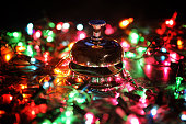 reception bell on the table and color shining garland on background