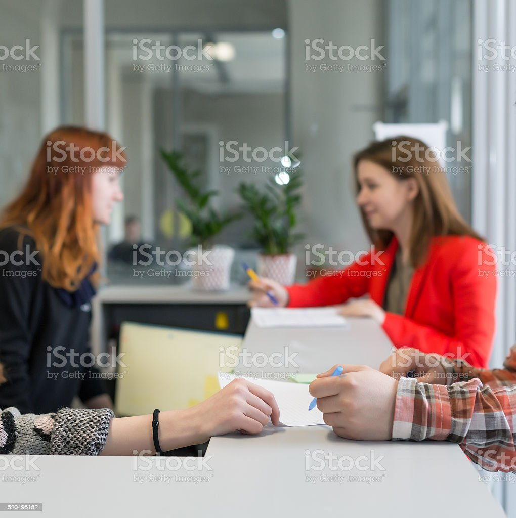 Reception Desk at Office Building Visitors talking to Secretaries stock photo