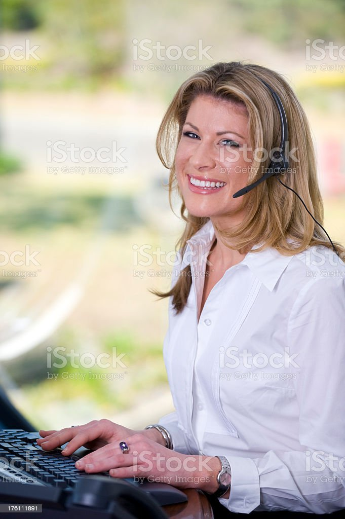 Receptionisit sitting at a computer royalty-free stock photo