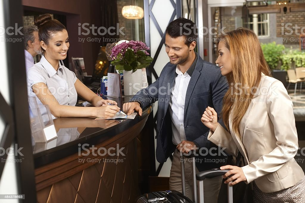 Receptionist and guests at hotel stock photo