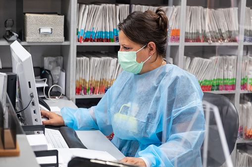 Hispanic receptionist at dental office wearing mask and gown for protection during the Covid-19 pandemic. She is working at the computer with patient files in the background.