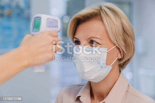 Receptionist checking fever middle age woman by digital thermometer for fever scan. Healthcare concept