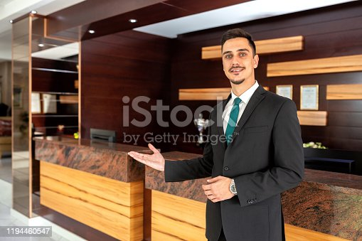 Receptionist dressed in fancy suit standing and welcoming guests