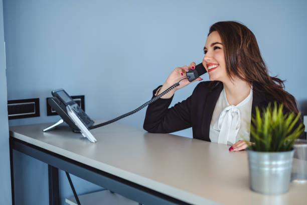 chica recepcionista habla por teléfono y sonriendo - recepcionista fotografías e imágenes de stock