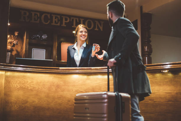 Receptionist giving keys to hotel guest stock photo
