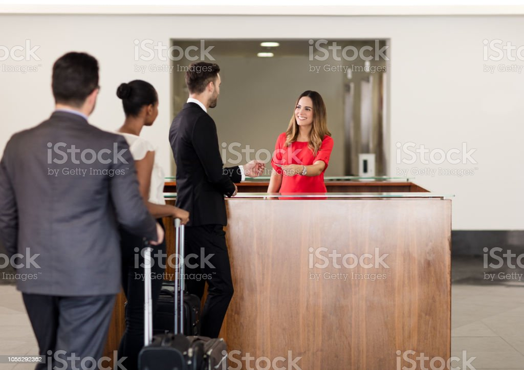 Receptionist helping business executives stock photo