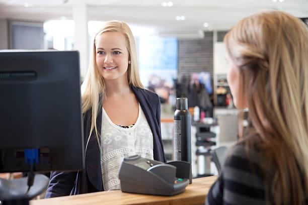 Receptionist Helping Customer at Beauty Salon stock photo