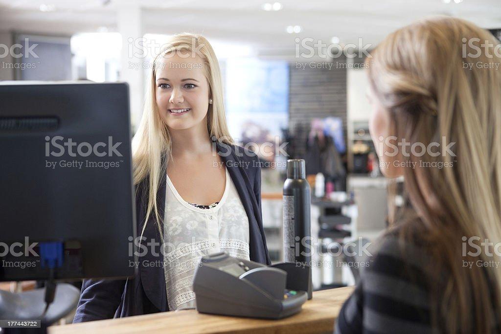 Receptionist aiutando il cliente presso il salone di bellezza - foto stock