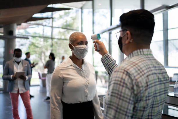 Receptionist measuring temperature of female employee at office's entrance - with face mask Receptionist measuring temperature of female employee at office's entrance - with face mask arrival stock pictures, royalty-free photos & images