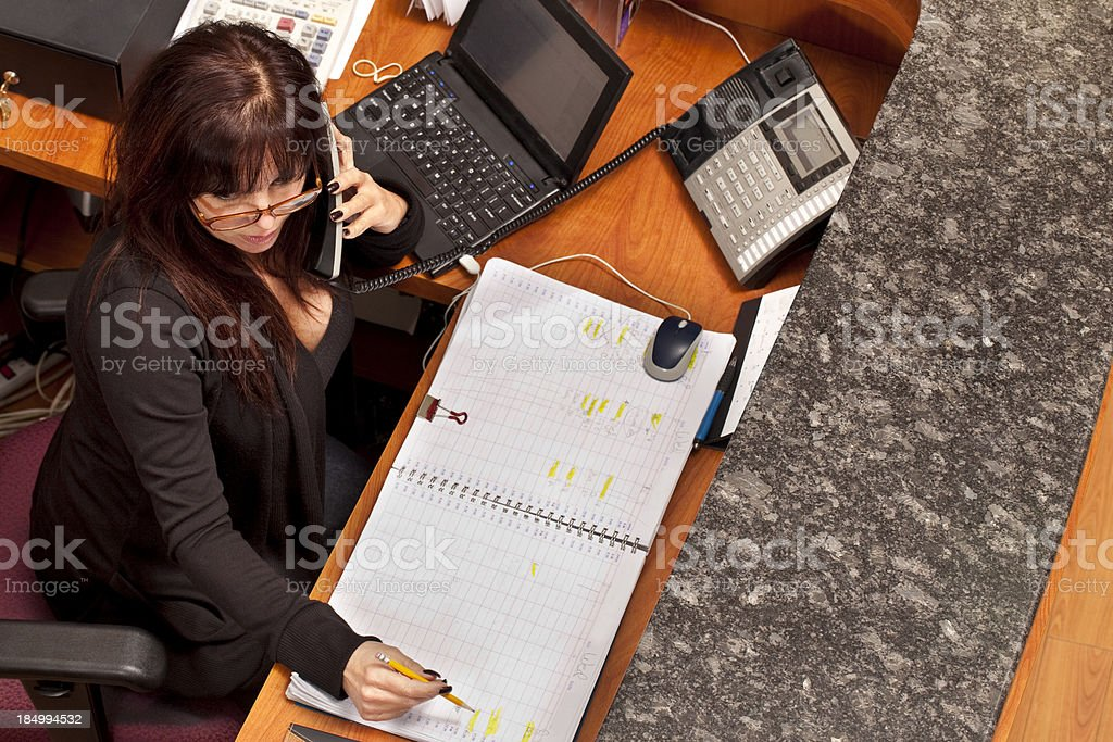 Receptionist on phone with at Hair Salon front desk royalty-free stock photo