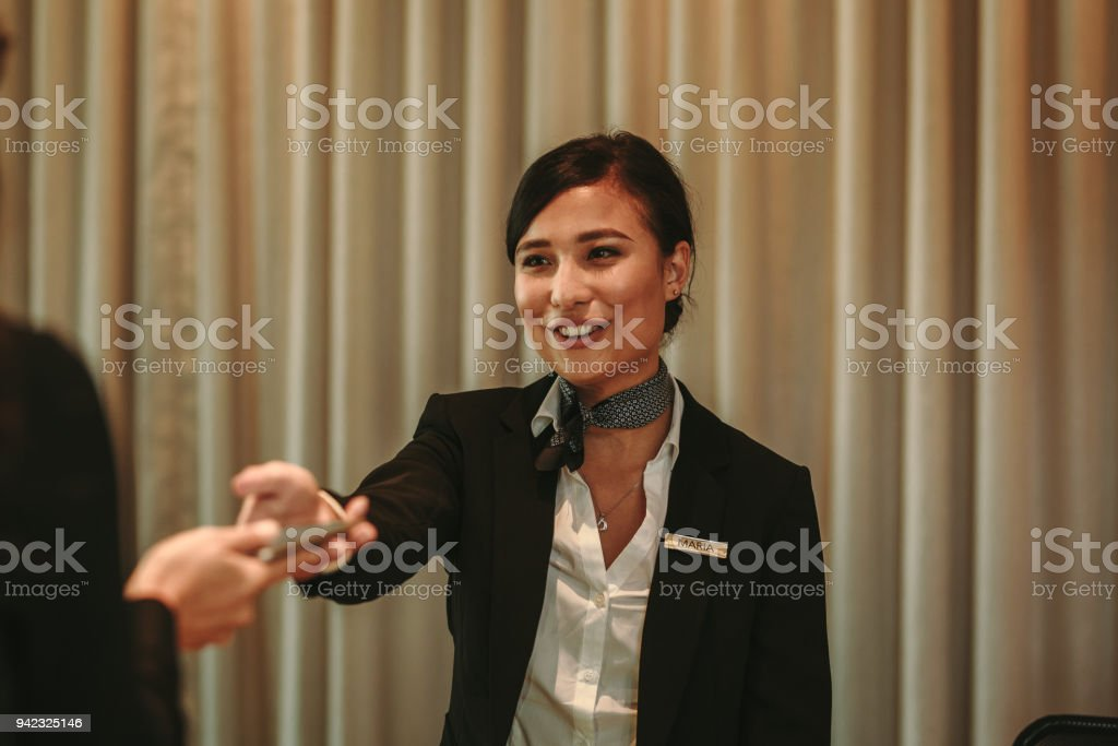 Receptionist receiving payment for hotel room from client stock photo