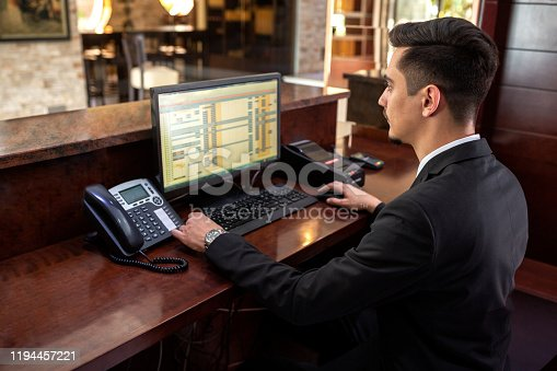 Receptionist sitting behind a front desk and looking at his monitor