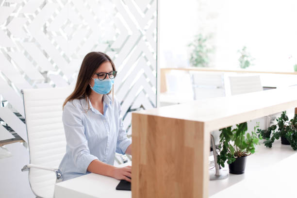 Receptionist wearing medical mask in office. Protection employees on workplace. Young woman working stock photo