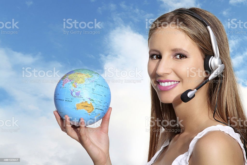 Receptionist with headphones and globe stock photo