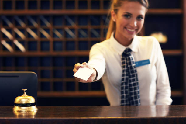 Receptionist with key card Picture of receptionist giving key card cardkey stock pictures, royalty-free photos & images