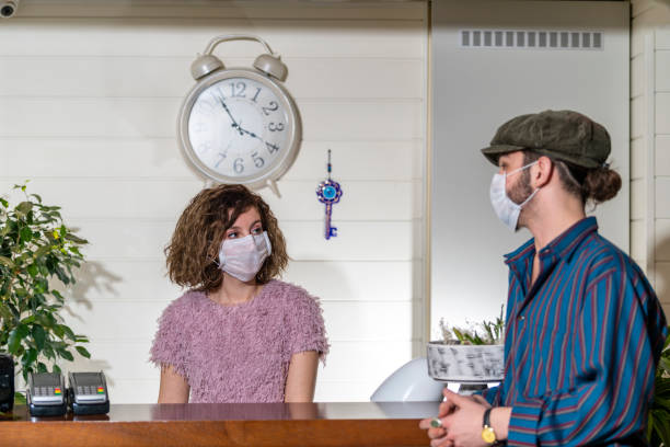 Receptionist woman and customer protected at the reception from epidemic disease stock photo