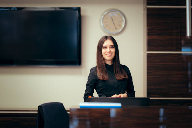 Receptionist Woman in front of Her Desk Greeting Customers Portrait of a front desk officer at her workplace checkout stock pictures, royalty-free photos & images