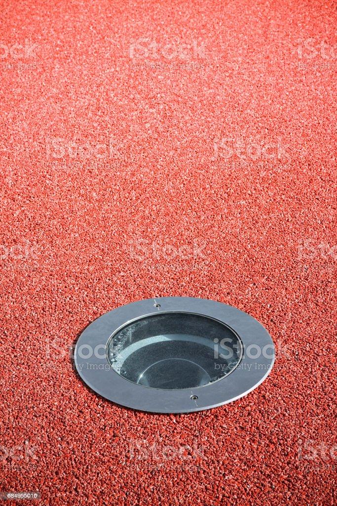 Recessed floor lamp on red gravel floor - image with copy space Lizenzfreies stock-foto
