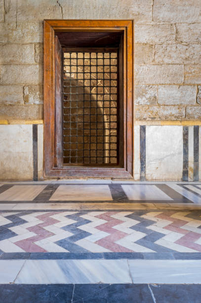 Recessed wooden window with decorated iron grid over stone bricks wall and decorative colorful floor stock photo