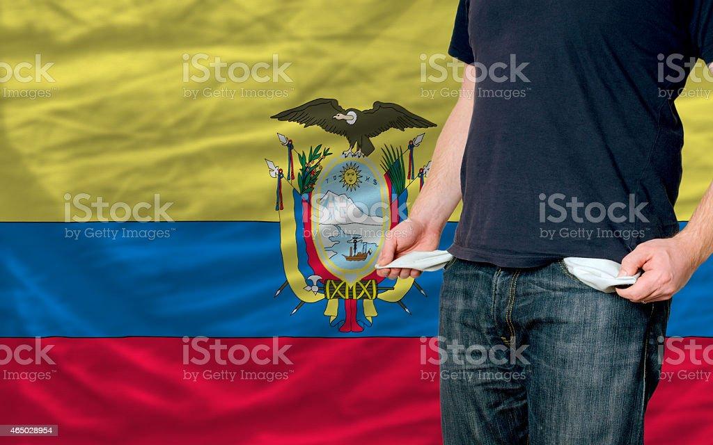 poor man showing empty pockets in front of ecuador flag
