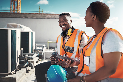 Shot of a young man and woman having a coffee break at a construction site