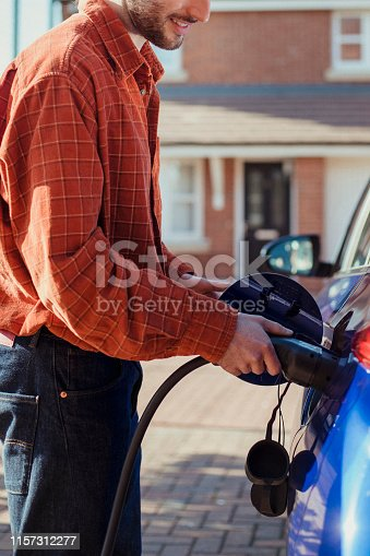 Man plugging a charger into his electric car at his home.