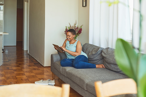 Shot of a young woman relaxing on the couch of her apartment while using a tablet