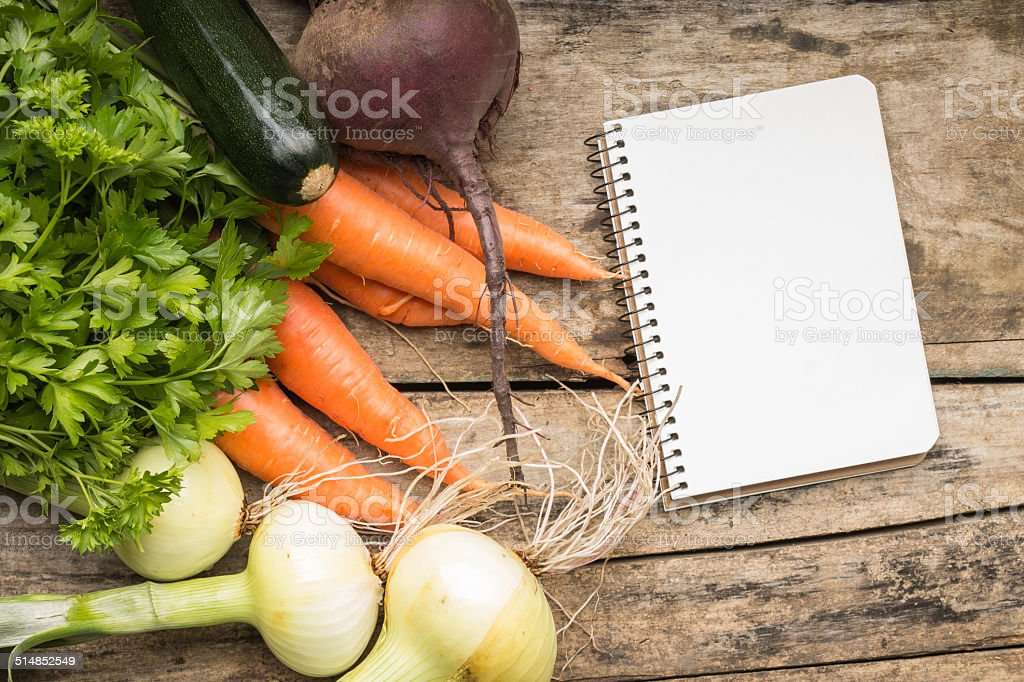 Recipe background. Fresh vegetables with blank page of cookbook stock photo