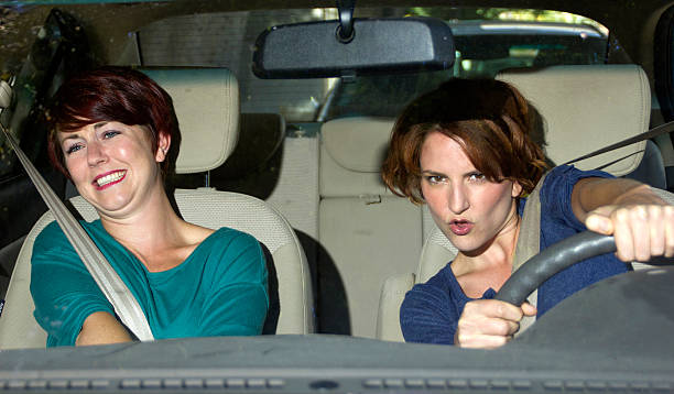 Reckless Driver with a Scared Passenger in the Car reckless driver and scared female passenger inside a car driving instructor stock pictures, royalty-free photos & images